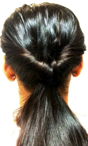 Create a low ponytail and part at rubber band and flip the ponytail through